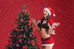圣诞老人衣裳的妇女在圣诞树附近的 库存图片