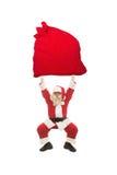 圣诞老人训练举非常与礼物的重的袋子 库存图片