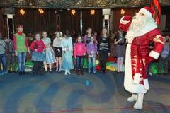 圣诞老人讲故事对一个小组孩子 运载圣诞节克劳斯礼品例证晚上圣诞老人向量 阶段的圣诞老人 免版税库存照片