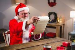 圣诞老人读书纸卷在客厅 库存图片