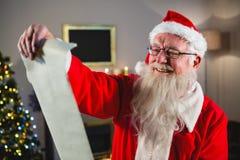 圣诞老人读书纸卷在客厅 免版税库存照片