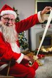 圣诞老人读书纸卷在客厅 图库摄影