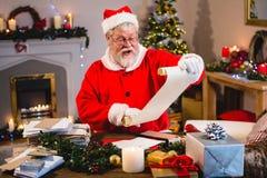 圣诞老人读书纸卷在客厅 免版税图库摄影