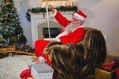 圣诞老人读书纸卷在客厅 库存照片