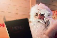 圣诞老人谈话在手机在餐馆 图库摄影