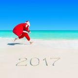 圣诞老人跑在与圣诞节大袋的热带海滩2017年 图库摄影