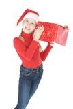 圣诞老人辅助工帽子的十几岁的女孩与礼品 库存照片