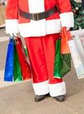 圣诞老人运载的购物袋 库存照片