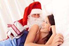 圣诞老人醒来的年轻美丽的妇女 免版税库存照片