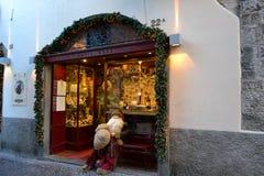 圣诞老人项目假与长的白色胡须坐街道藤商店的铁长凳 免版税库存照片