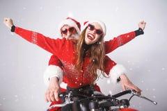 圣诞老人项目和年轻夫人 乘坐A的克劳斯摩托车 免版税库存图片