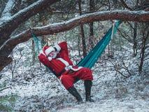 圣诞老人项目在吊床在积雪的冬天前面 免版税库存照片