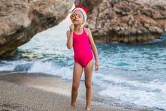 圣诞老人项目帽子和棒棒糖的在海滩,自由空间逗人喜爱的女孩 图库摄影