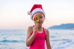 圣诞老人项目帽子和棒棒糖的在海滩,自由空间逗人喜爱的女孩 免版税库存图片
