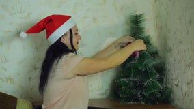 圣诞老人项目帽子的一年轻女人在家装饰一棵圣诞树 影视素材