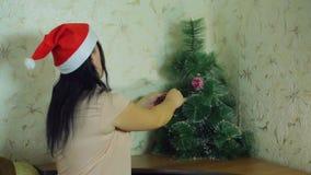 圣诞老人项目帽子的一年轻女人在家装饰与欢乐气球的圣诞树 股票视频