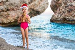 圣诞老人项目帽子的美丽的女孩庆祝在海滩的新年 库存照片