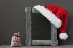 圣诞老人项目帽子,礼物袋子和木制框架 库存照片