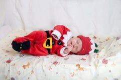 圣诞老人项目服装的婴孩睡觉在床上的 免版税库存图片