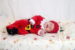 圣诞老人项目服装的婴孩睡觉在床上的 库存图片