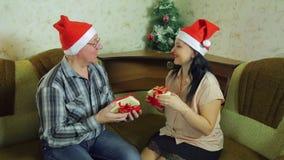 圣诞老人项目的恋人男人和妇女加盖在平安夜的交换圣诞礼物 平均计划 股票视频