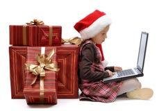 圣诞老人项目盖帽的女孩有膝上型计算机和圣诞礼物的 库存照片