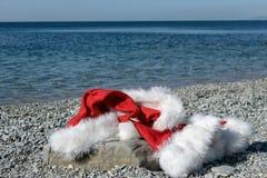 圣诞老人项目衣物和在一块大石头的帽子谎言在海滨 圣诞老人去游泳 库存照片