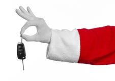 圣诞老人题材:把握关键的圣诞老人的手对在白色背景的一辆新的汽车 免版税库存照片