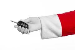 圣诞老人题材:把握关键的圣诞老人的手对在白色背景的一辆新的汽车 免版税图库摄影