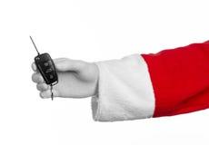 圣诞老人题材:把握关键的圣诞老人的手对在白色背景的一辆新的汽车 免版税库存图片