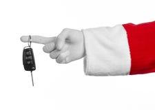 圣诞老人题材:把握关键的圣诞老人的手对在白色背景的一辆新的汽车 图库摄影