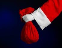 圣诞老人题材:拿着有礼物的圣诞老人一个大红色大袋在深蓝背景 免版税库存图片