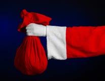 圣诞老人题材:拿着有礼物的圣诞老人一个大红色大袋在深蓝背景 免版税库存照片
