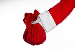 圣诞老人题材:拿着有礼物的圣诞老人一个大红色大袋在白色背景 免版税库存图片