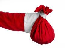 圣诞老人题材:拿着有礼物的圣诞老人一个大红色大袋在白色背景 免版税库存照片