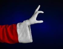 圣诞老人题材:显示在深蓝背景的圣诞老人的手姿态 图库摄影
