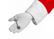 圣诞老人题目:手圣诞老人把握关键到一栋新的公寓或一个新房白色背景的 图库摄影