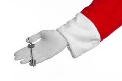 圣诞老人题目:手圣诞老人把握关键到一栋新的公寓或一个新房白色背景的 免版税库存照片