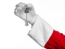 圣诞老人题目:手圣诞老人把握关键到一栋新的公寓或一个新房白色背景的 免版税库存图片