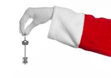 圣诞老人题目:手圣诞老人把握关键到一栋新的公寓或一个新房白色背景的 免版税图库摄影
