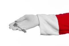 圣诞老人题目:手圣诞老人把握关键到一栋新的公寓或一个新房白色背景的 库存照片
