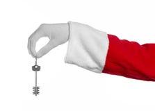 圣诞老人题目:手圣诞老人把握关键到一栋新的公寓或一个新房白色背景的 库存图片