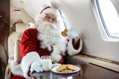 圣诞老人饮用曲奇饼和牛奶在私人喷气式飞机 图库摄影