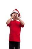 圣诞老人饮用水帽子的滑稽的小男孩一块玻璃的在白色背景 免版税库存照片