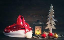 圣诞老人,圣诞节灯和玻璃球形圣诞节帽子与一棵木装饰新年树在木背景 免版税库存照片