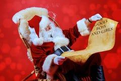 圣诞老人读一个纸卷 库存图片