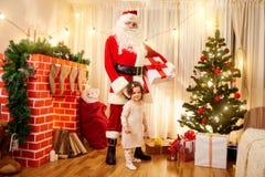 圣诞老人给一件礼物一个孩子在有装饰的屋子里, 库存图片