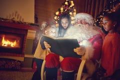 圣诞老人读书不可思议的圣诞节童话 图库摄影