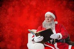圣诞老人读书圣经的综合图象 免版税图库摄影