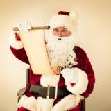 圣诞老人读书纸卷 库存照片